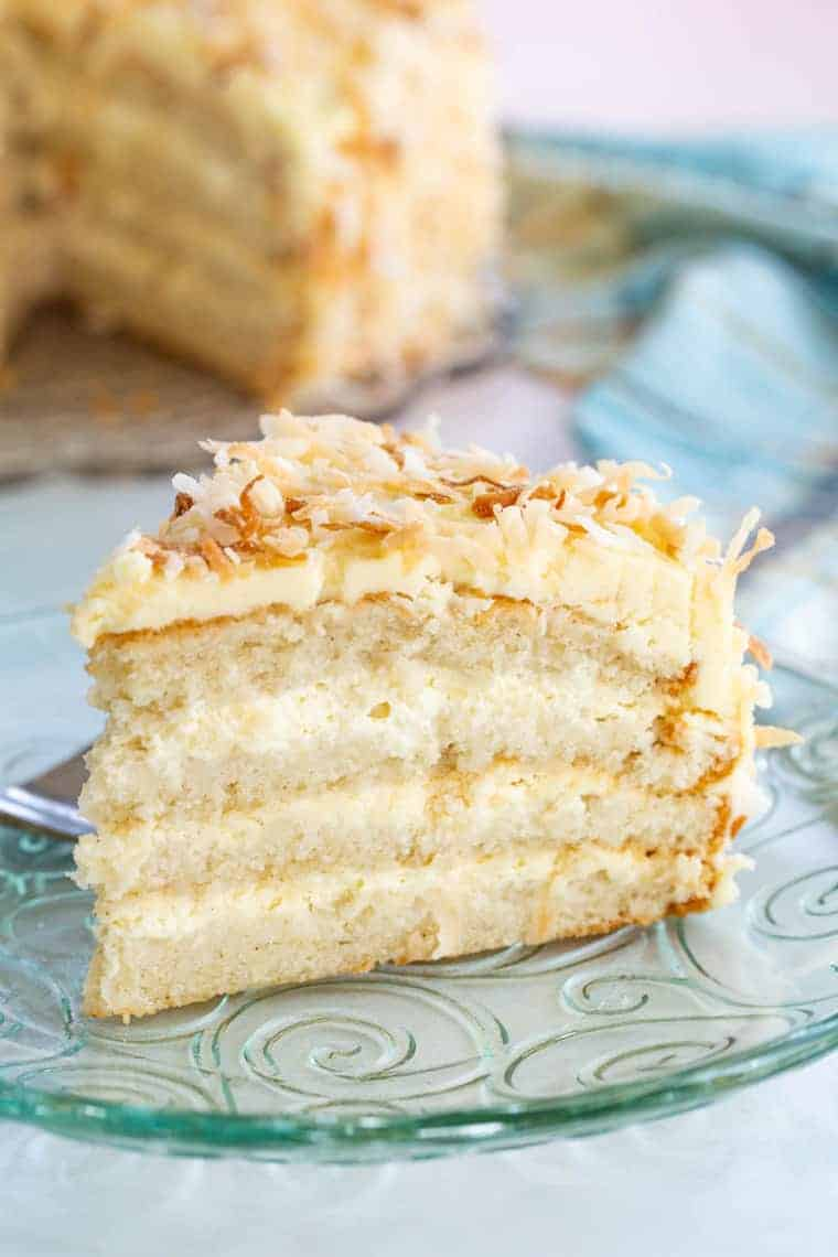 Piece of gluten free coconut cake from the side to see layers of cake, filling, and coconut buttercream frosting