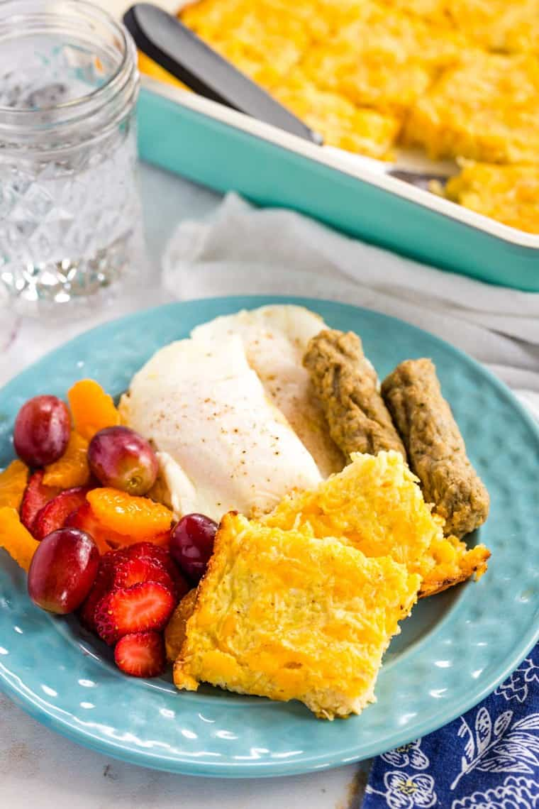 Squares of Cheesy Cauliflower Hash Browns Casserole on a plate with sausage, eggs, and fruit