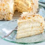 Gluten free white cake with coconut filling and frosting on a glass plate