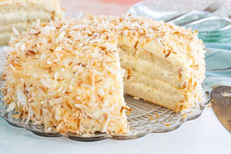Gluten Free Toasted Coconut Cake on a platter with a slice removed