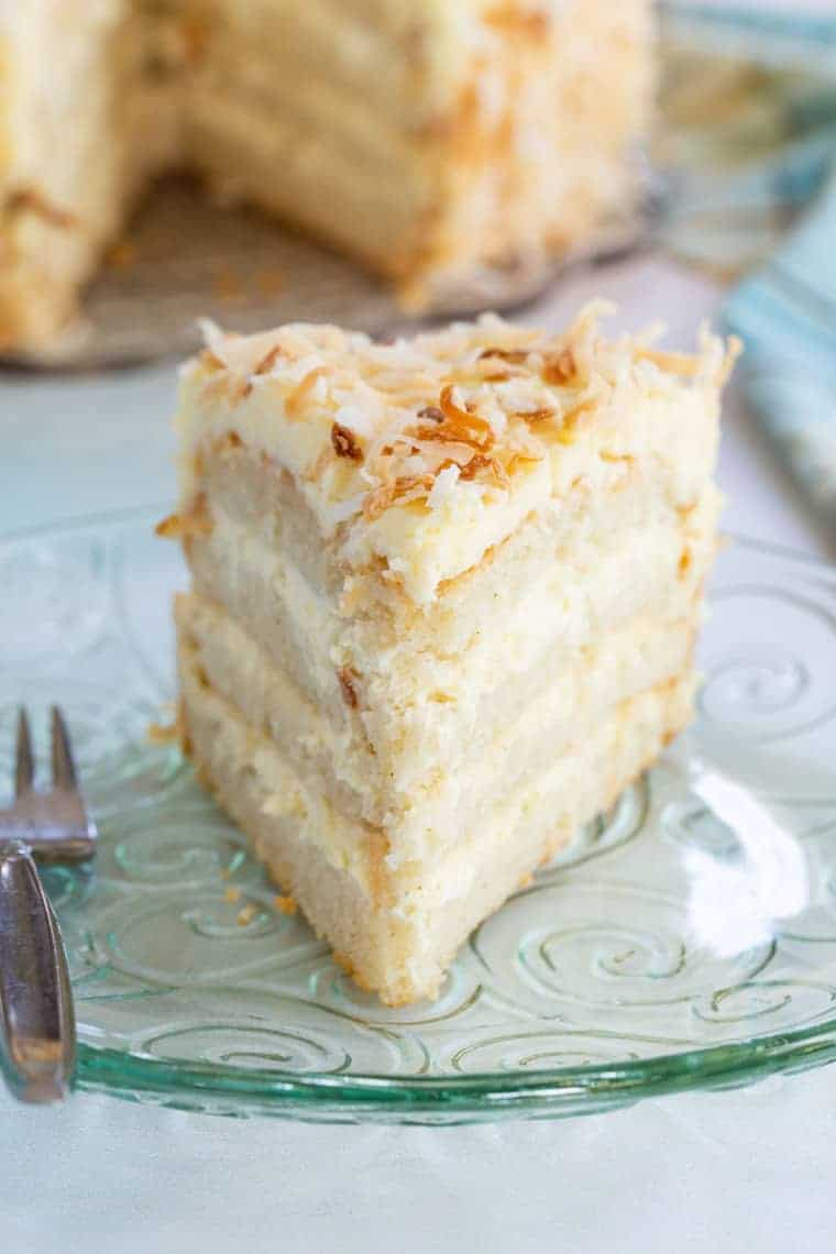 Slice of gluten free white cake with coconut buttercream from the front
