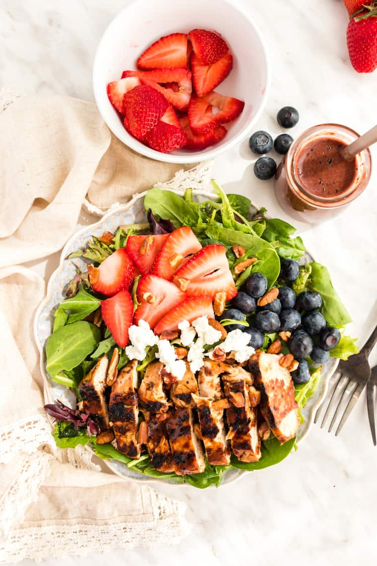 Sliced Grille Chicken Salad topped with berries and goat cheese with a bottle of blueberry balsamic salad dressing