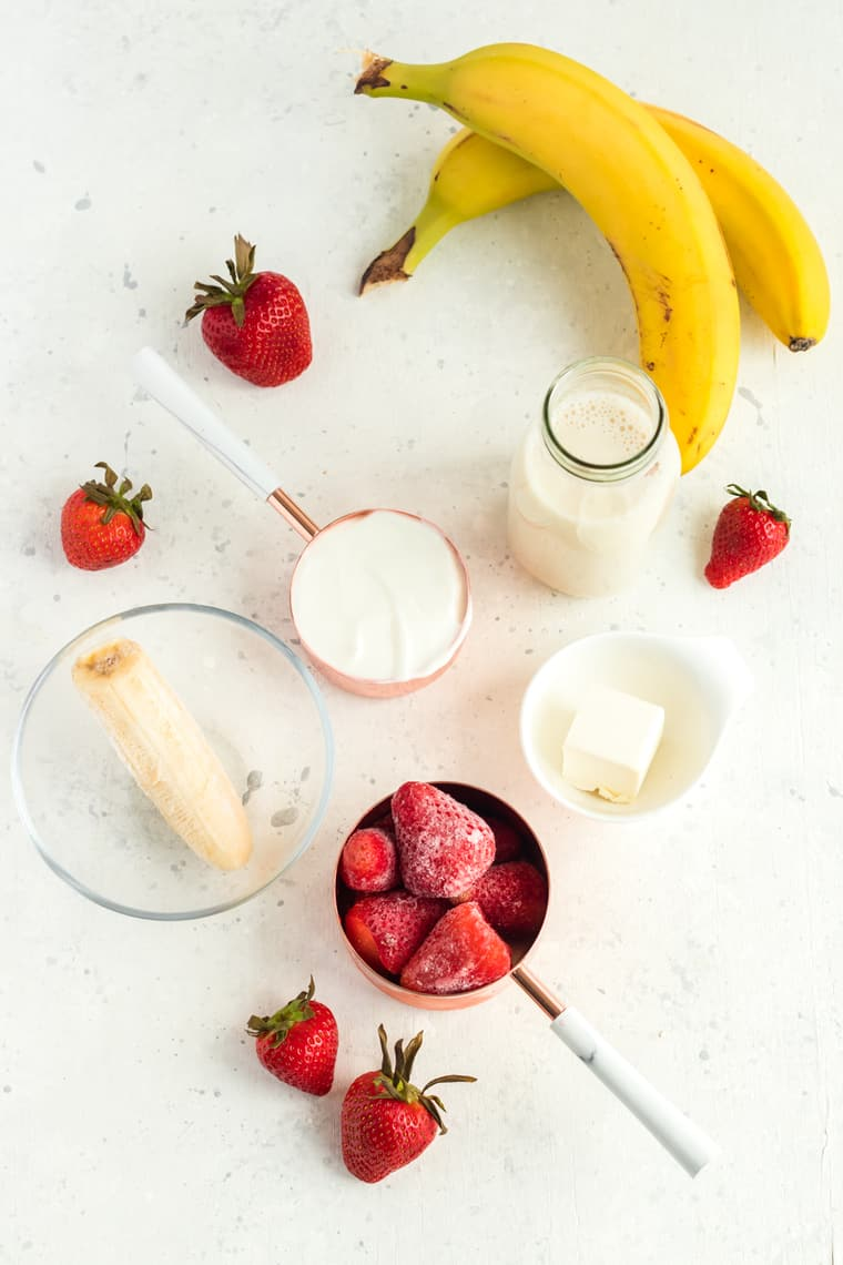 Table with ingredients to make a Strawberry Cheesecake Smoothie