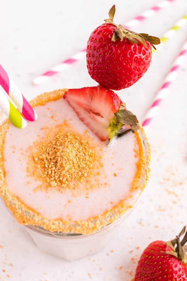 Top of a Strawberry Cheesecake Smoothie in a glass garnished with graham cracker crumbs