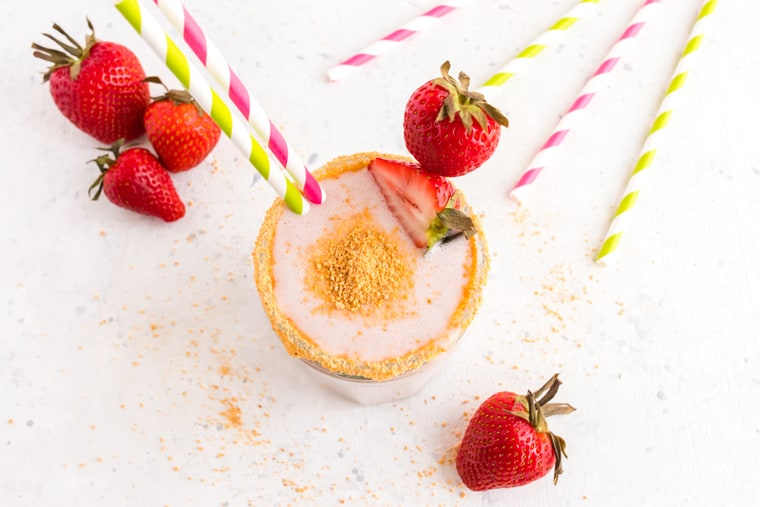 Overhead of a Strawberry Cheesecake Smoothie surrounded by strawberries and striped straws