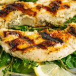 Closeup of a piece of grilled chicken laying on a pile of greens, herbs, and lemon slices