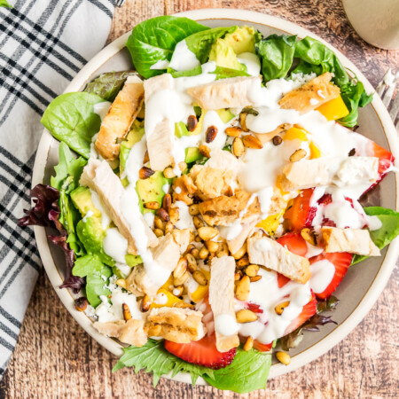 Overhead horizontal image of grilled chicken salad with strawberries and mango