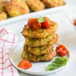 Stack of gluten free zucchini fritters on a white plate with roasted balsamic tomatoes topping
