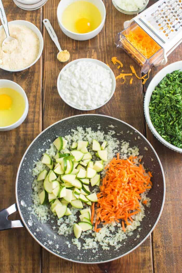 Cooking onions, carrots and zucchini in a skillet until soft