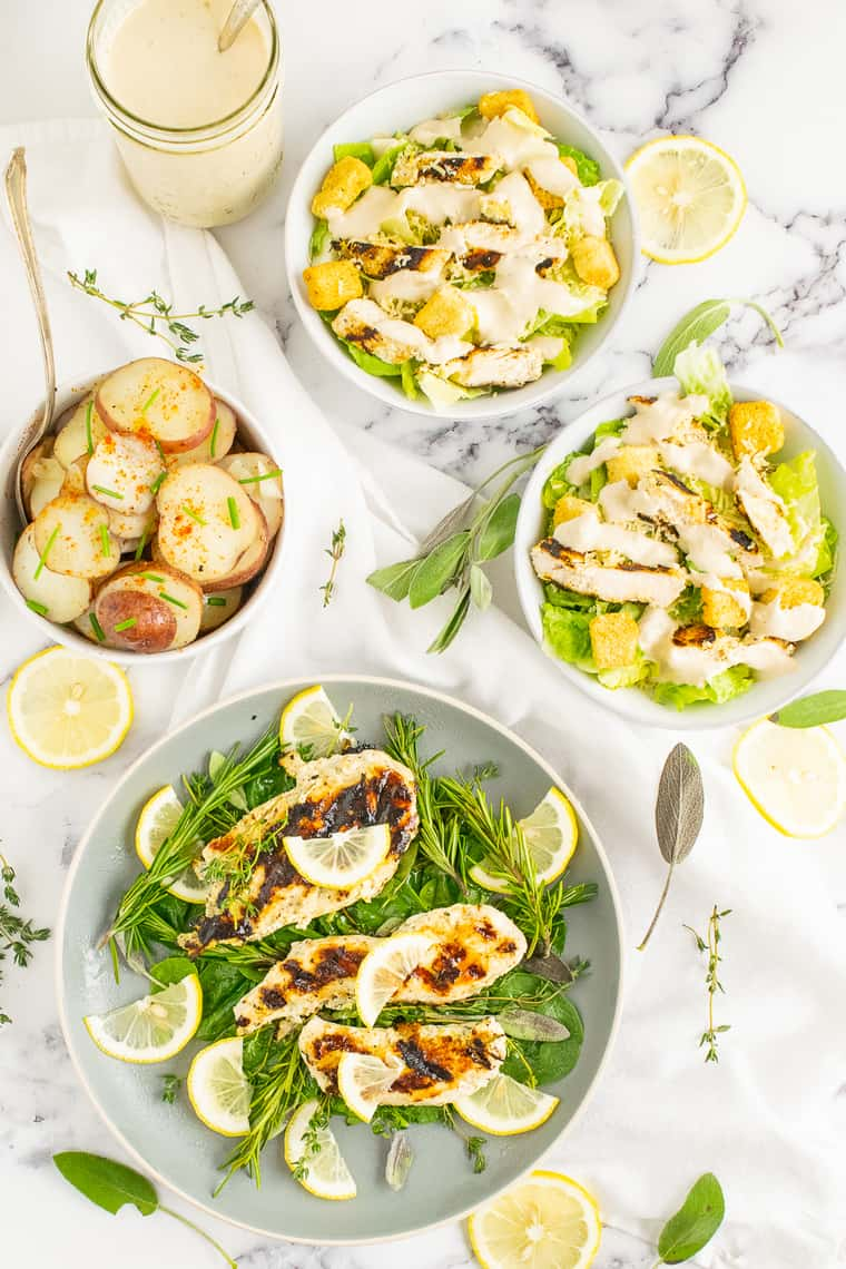 A dinner featuring lemon herb grilled chicken, caesar salad, and potatoes
