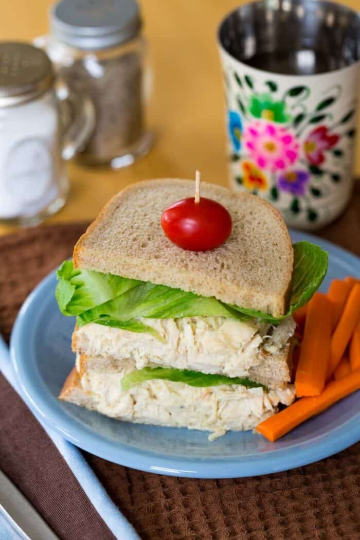 Honey Dijon Chicken Salad Sandwich with carrots on a blue plate