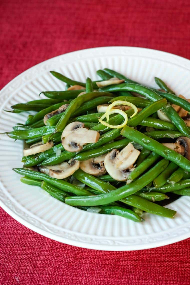 Lemon Butter Green Beans and Mushrooms served in a bowl on a red placemat