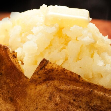 Close up of a baked potato cut open with a pat of butter