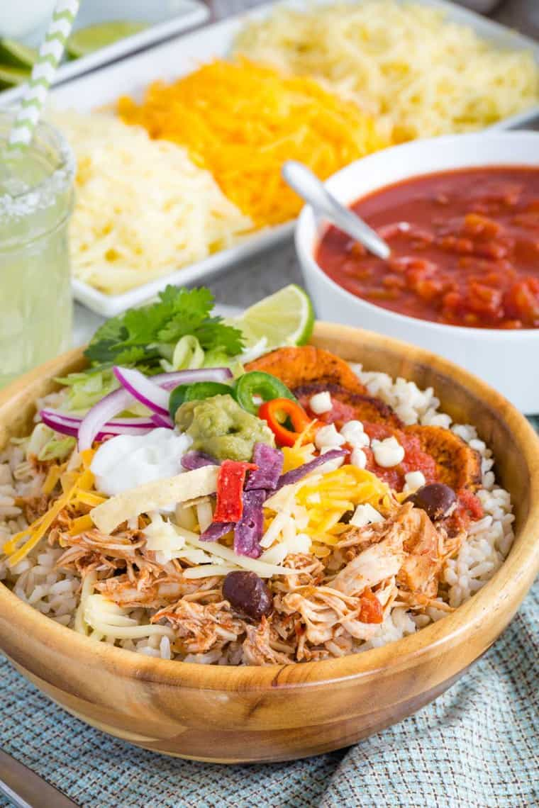 Chicken Burrito Bowl with shredded cheese, tortilla chips, salsa, and more on top