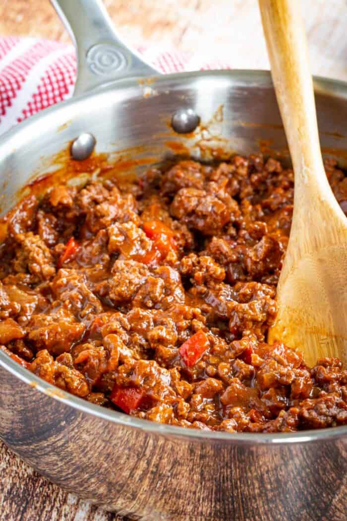 Pan with ground beef sloppy joes meat and a wooden spoon