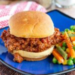 Easy sloppy joe on a blue plate with vegetables