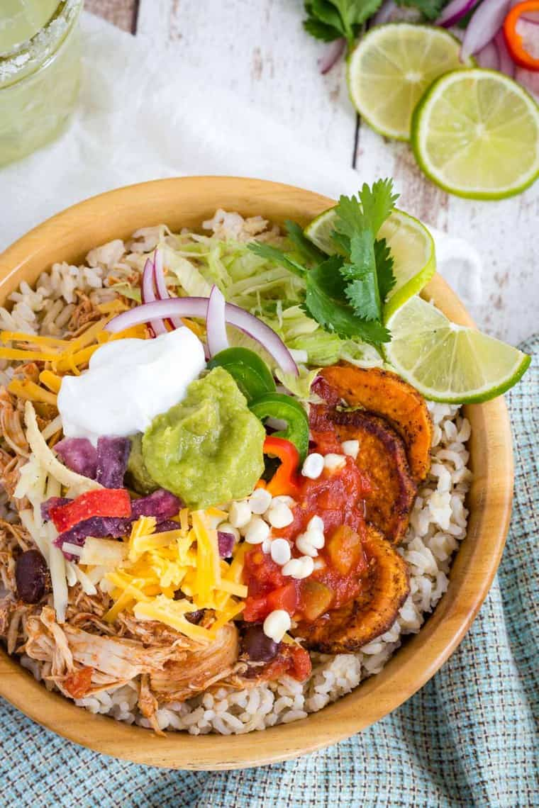 Salsa Chicken Rice Bowl with cheese, corn, tortilla chips, lime, lettuce and more on top
