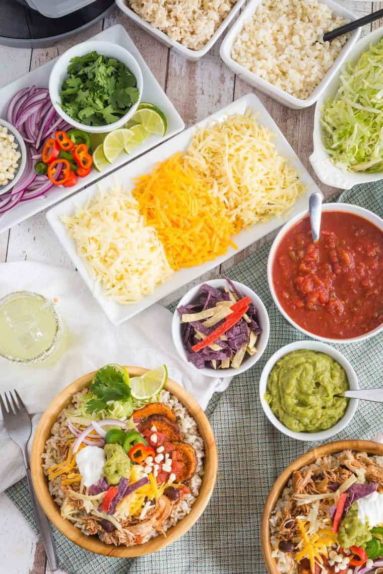 Bowls and plates of toppings to make burrito bowls