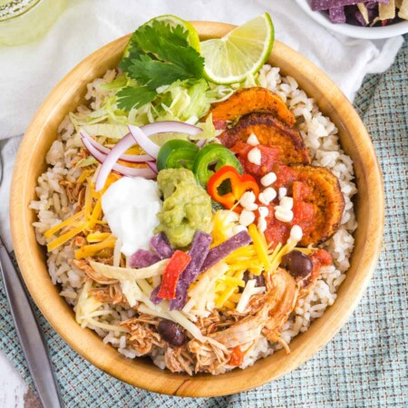 Chicken Burrito Bowl with toppings and garnished with lime and cilantro