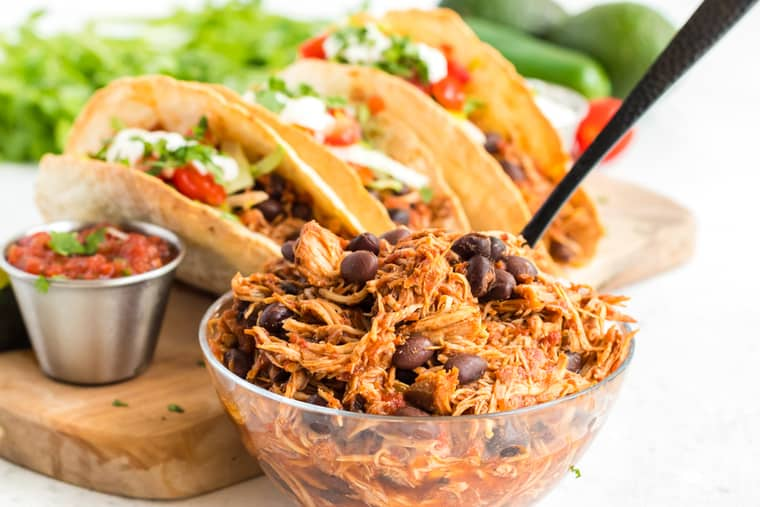 shredded chicken with black beans in a bowl with tacos in the background