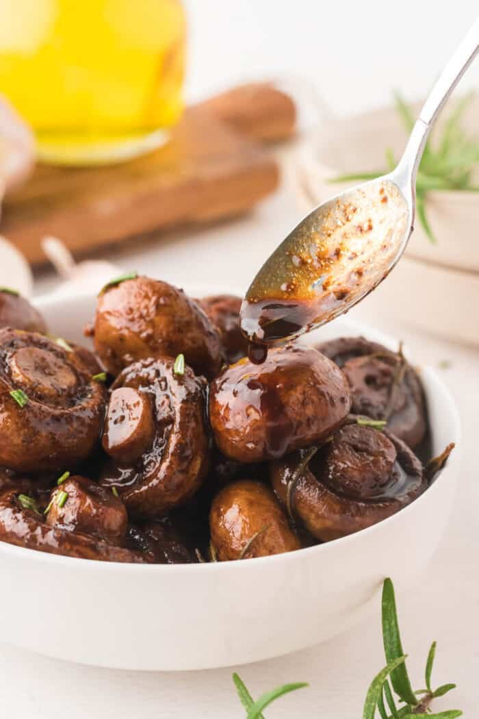 Drizzling balsamic glaze over garlic roasted mushrooms