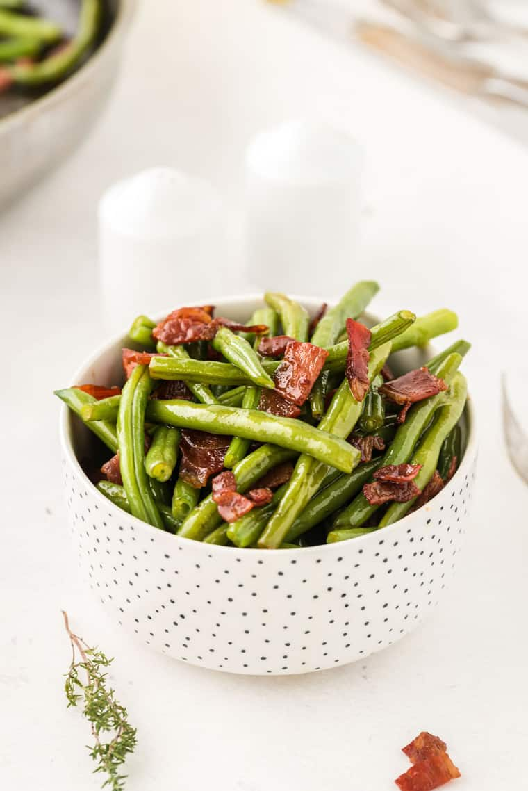 Small white serving bowl of green beans with bacon