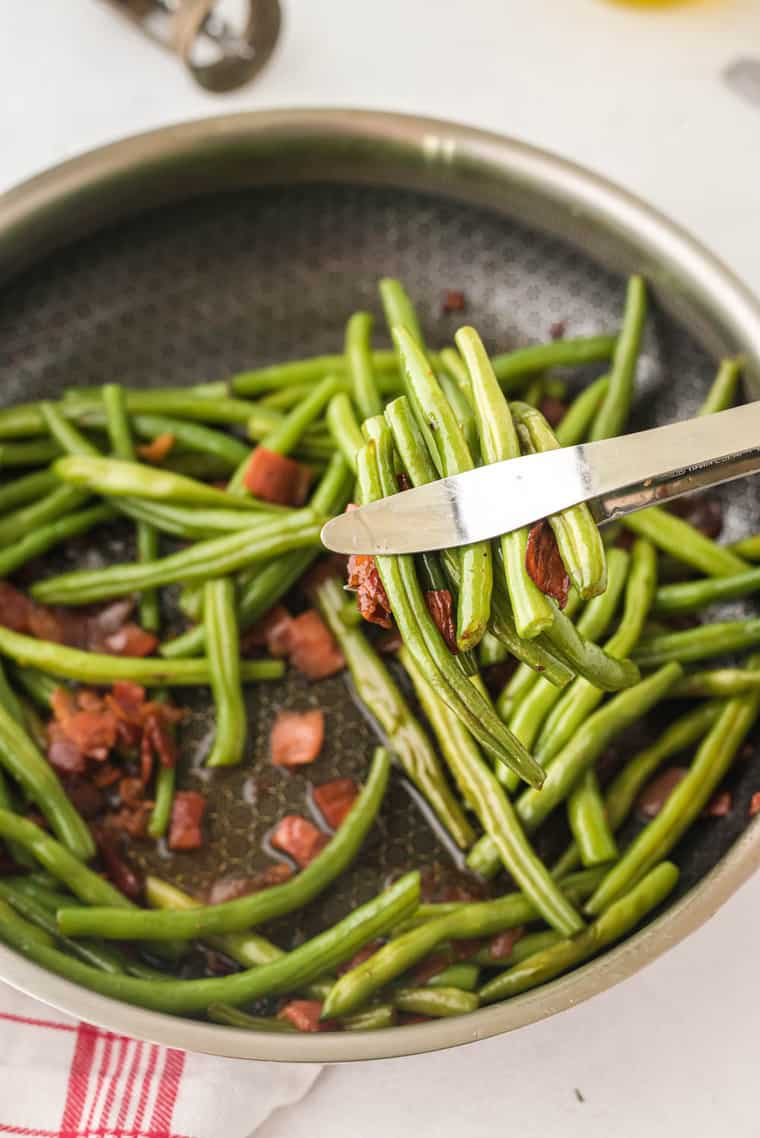 Picking up Bacon Green Beans with tongs
