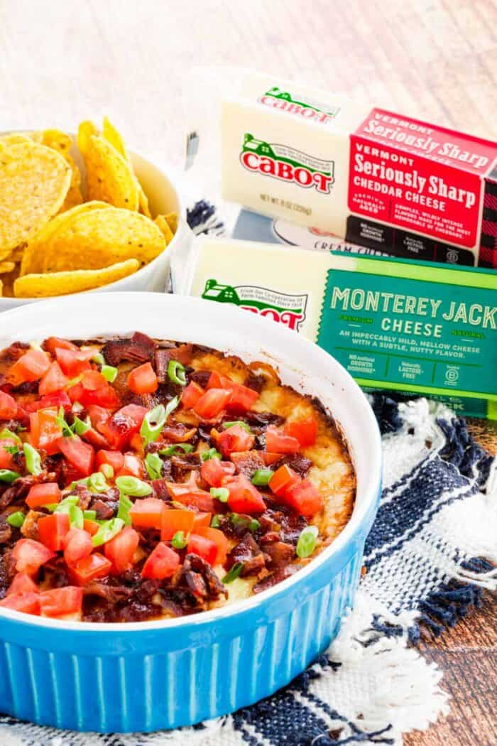 Cheesy dip topped with bacon and tomatoes in a baking dish with packages of Cabot Seriously sharp cheddar and Monterey Jack cheese and cream cheese