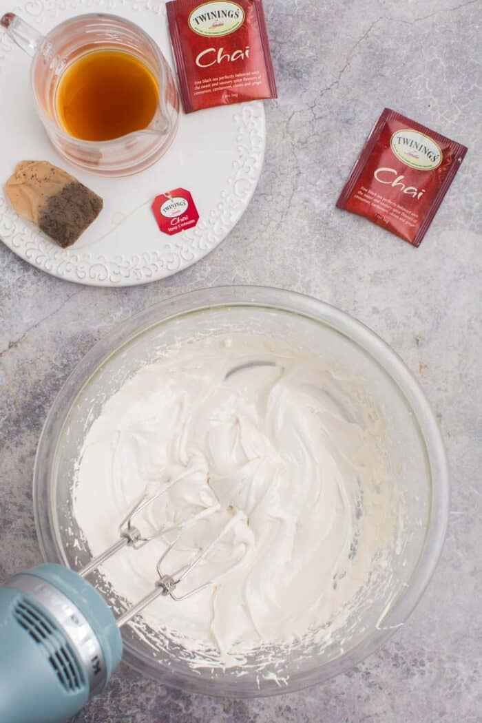 Brewed chai tea next to a bowl of chai royal icing being blended with a hand mixer