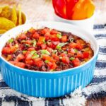 Hot dip in a casserole with bowls of bell pepper slices and tortilla chips