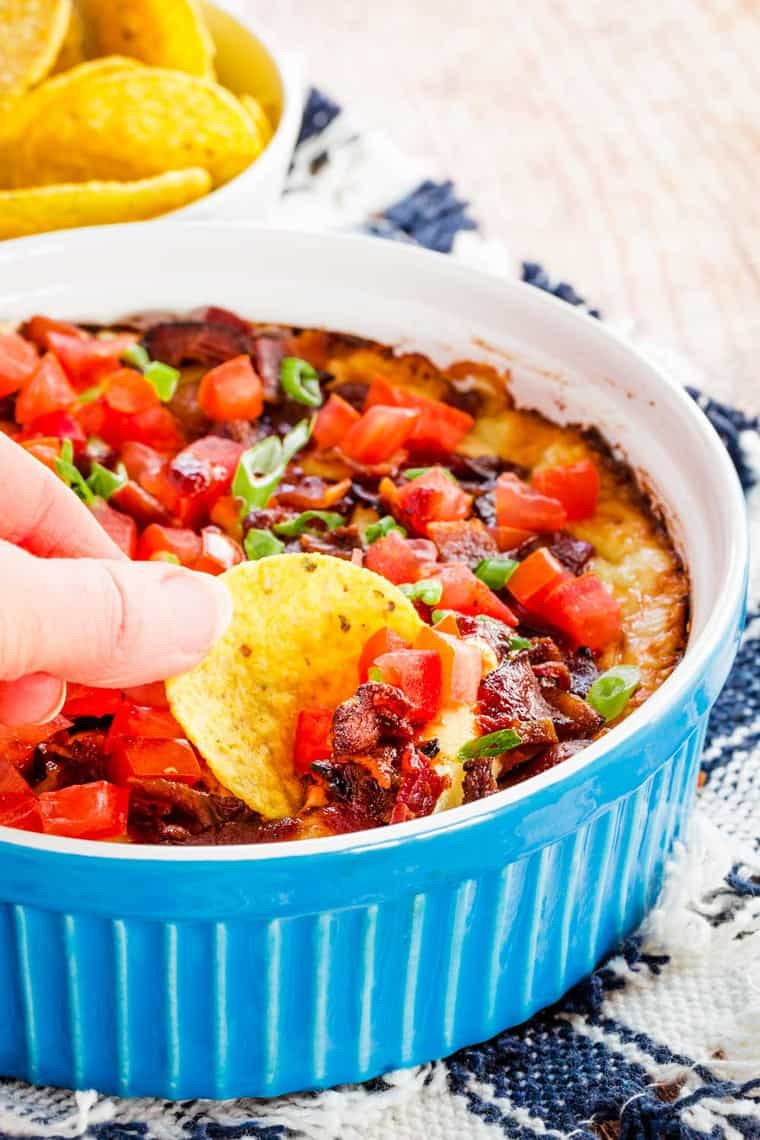 fingers holding a chip loaded with dip, bacon, and tomatoes