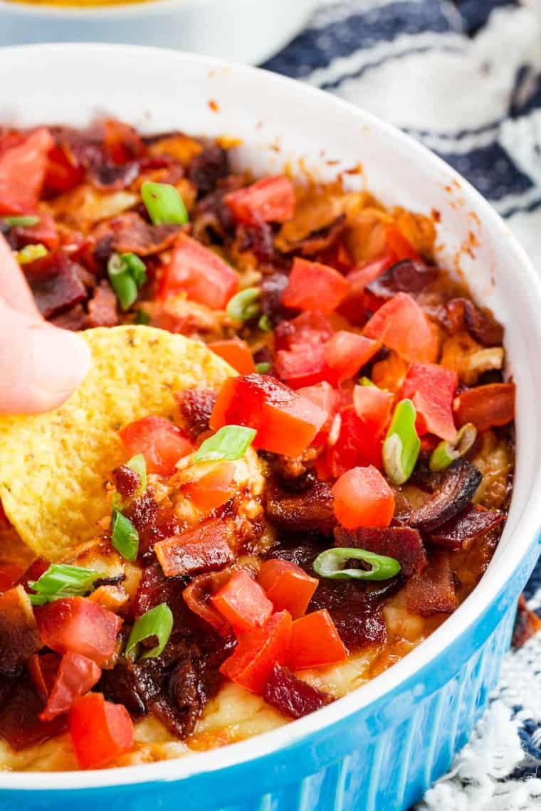 Tortilla chip scooping up BBQ chicken dip with bacon