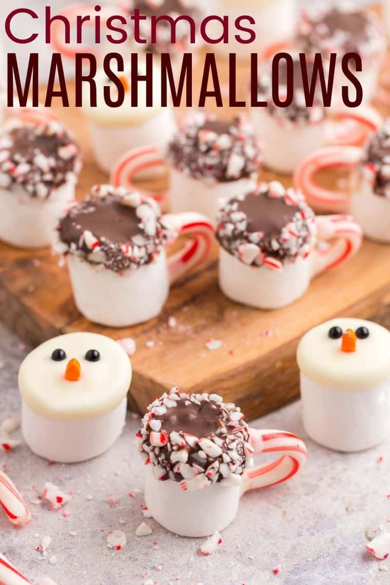 A platter of Christmas marshmallows dipped in marshmallows and decorated like snowmen and hot cocoa mugs.
