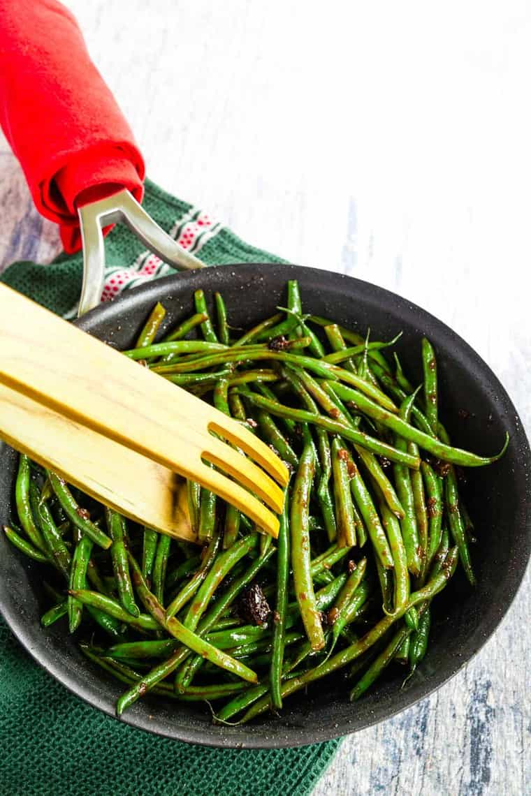 Scooping Balsamic Green Beans out of a skillet with wooden tongs