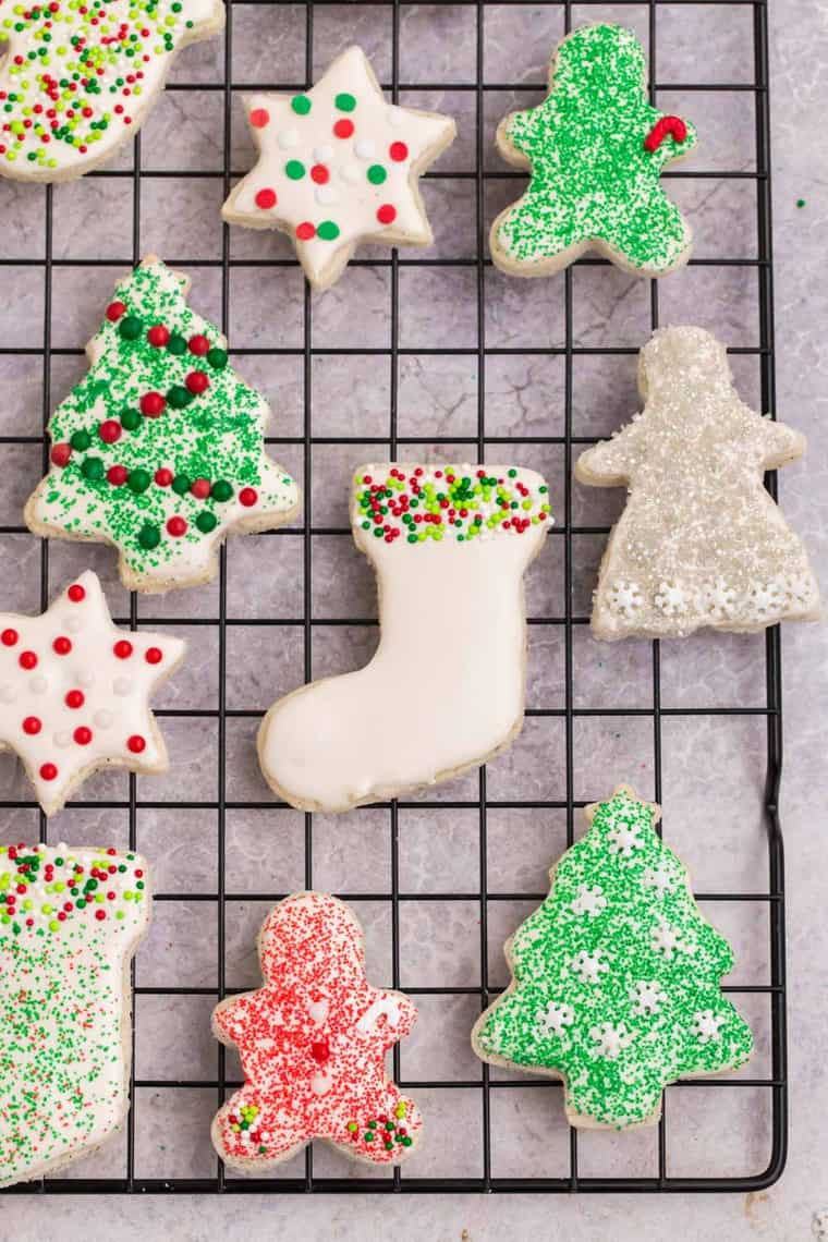 A cooling rach with cut out sugar cookies decorated with frosting and sprinkle sin Christmas colors