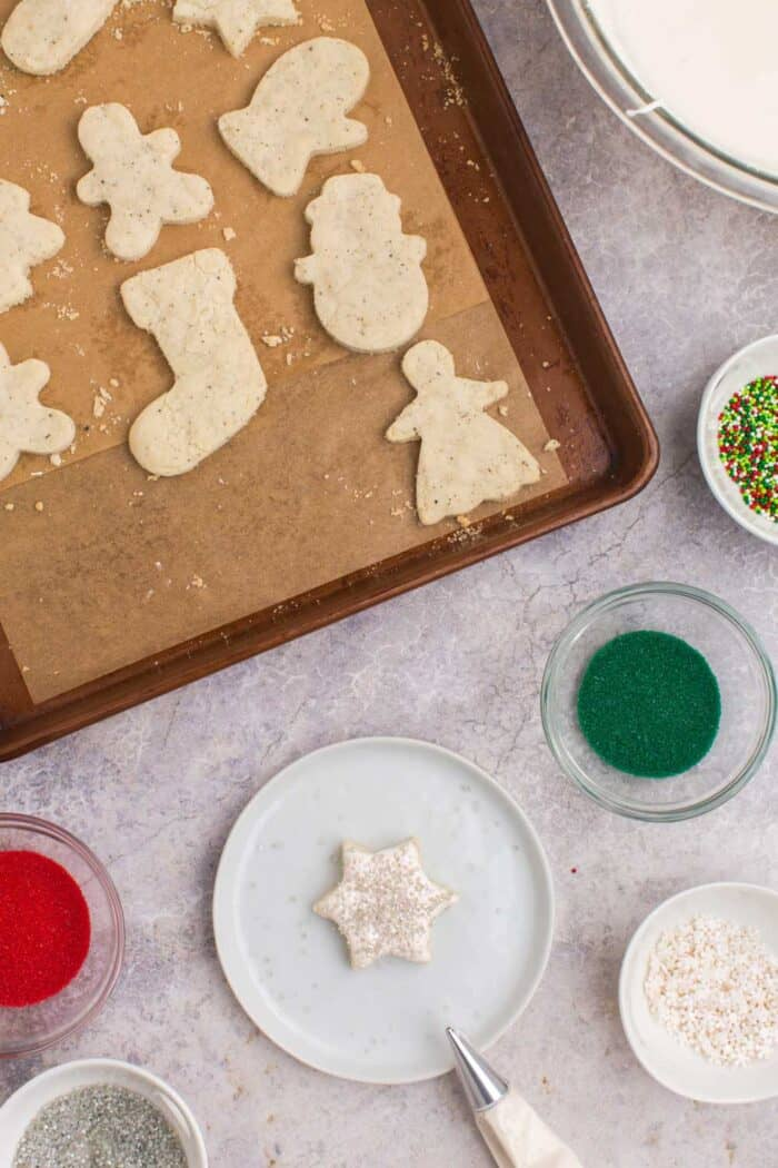 Piping bag next to a star-shaped Chai cookie decorated with white icing and silver sprinkles