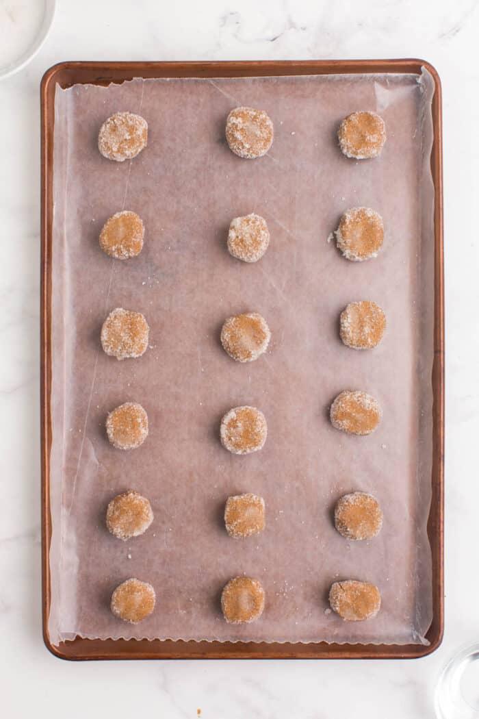 18 balls of gluten free gingersnap cookie dough on a baking sheet