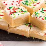 Gluten Free Sugar Cookie Bars with Christmas sprinkles on a slate platter