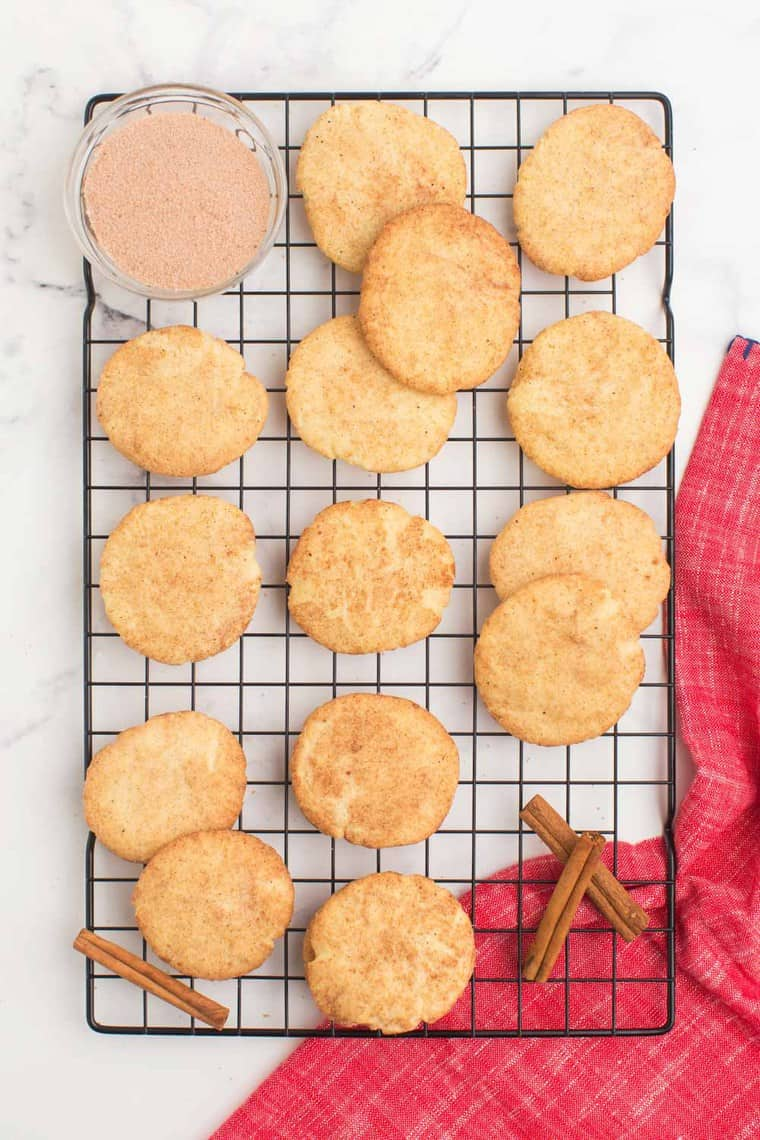 13 snickerdoodles scattered on a cooling rack with a bowl of cinnamon sugar on the side