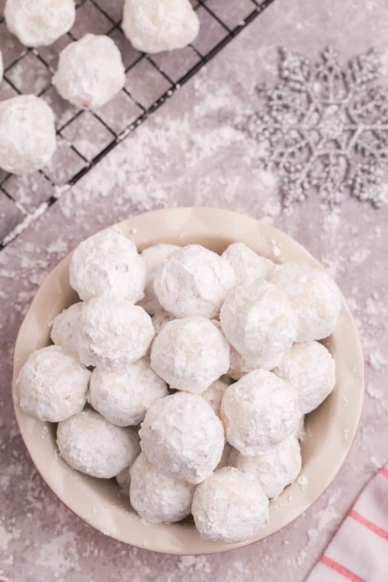 Looking down at a bowl of snowball cookies on a table covered in powdered sugar