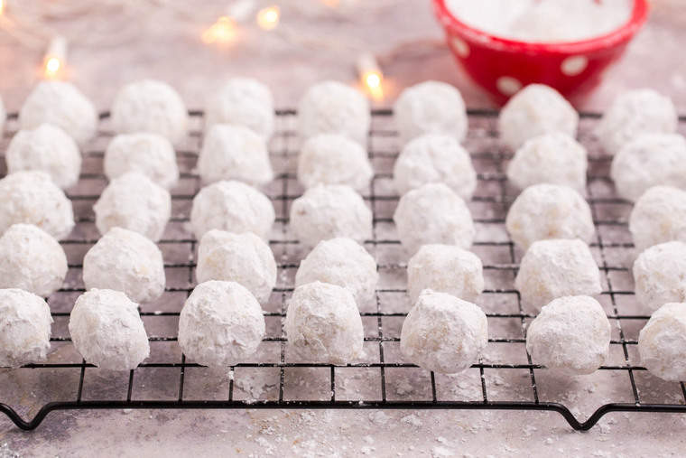 Snowball Cookies on a cooling rack and a red bowl of powdered sugar