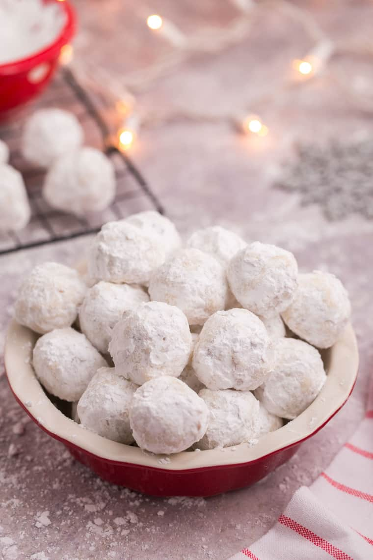 Red ball of snowball cookies with Christmas lights in the background