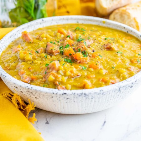 bowl of split pea soup on a marble table with a spoon and yellow cloth napkin