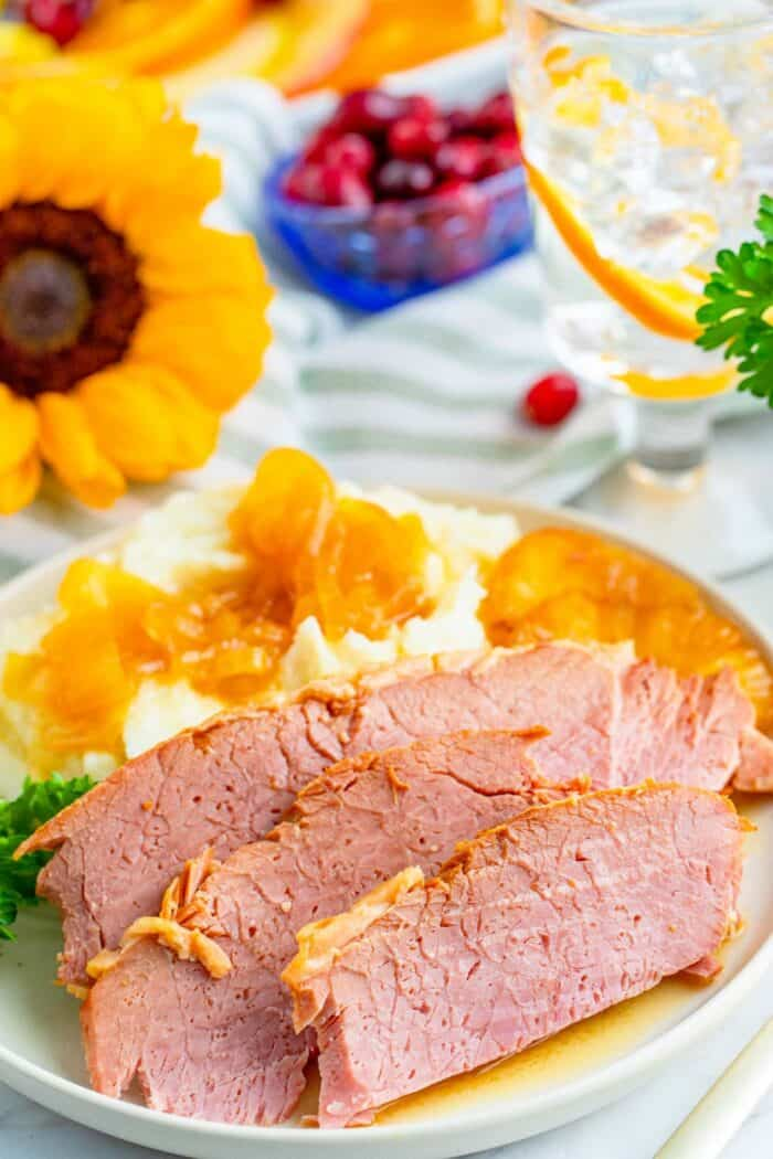Three slices of ham on a white plate with mashed potatoes