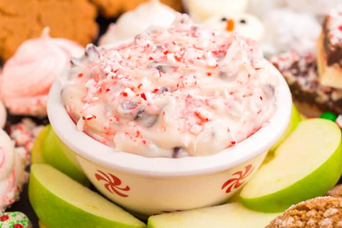 Bowl of peppermint cheesecake dip surrounded by apple slices and cookies