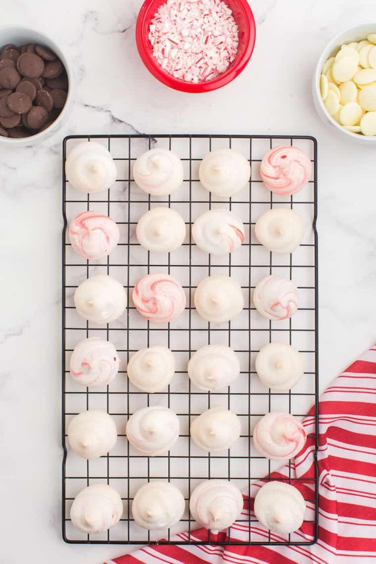 Baked peppermint meringues on a cooling rack with chocolate and candy canes in bowls for dipping