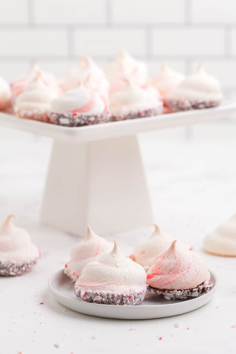A small plate of peppermint meringues with more on a cake stand in the background