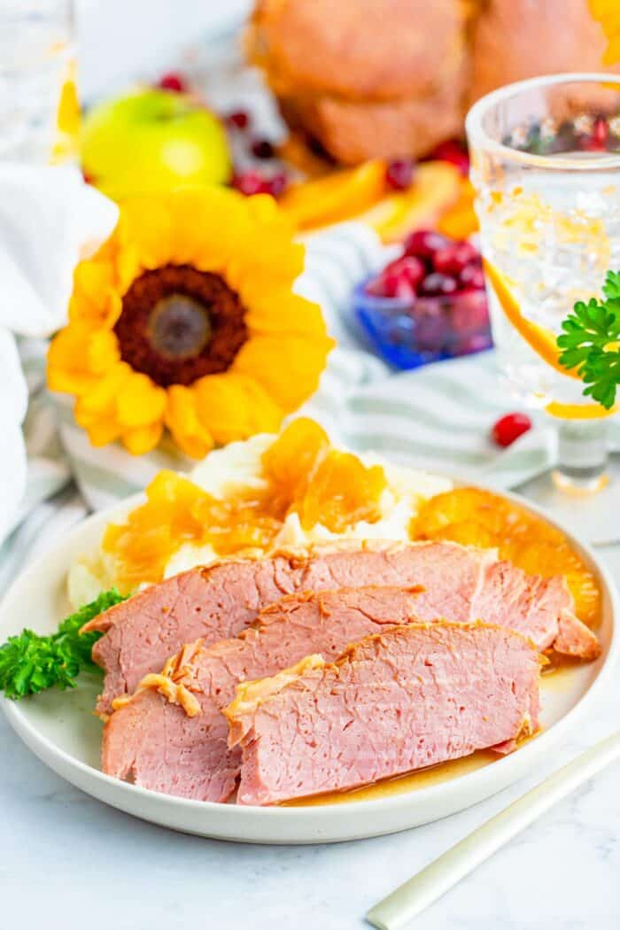 Sliced ham on a plate with mashed potatoes set on a table with a glass of water