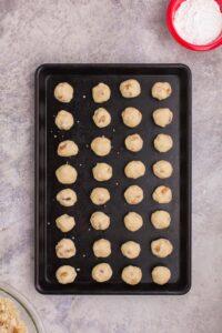 raw balls of snowball cookie dough on a baking sheet