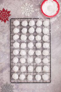 Snowball cookies on a cooling rack after being rolled in powdered sugar